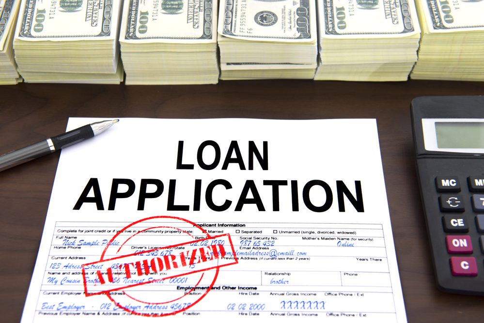 Approved loan application form and stacks of 100 dollar bills
